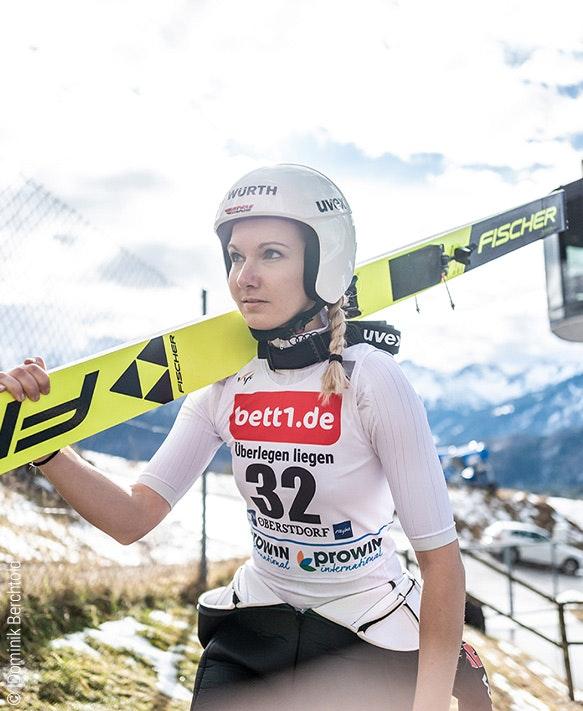 Photo : Une sauteur à ski épaule ses skis ; publicité pour bett1 sur son maillot.