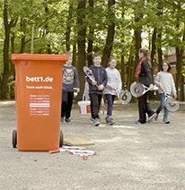 Photo : Au premier plan une poubelle rouge, au second plan des enfants avec des raquettes de tennis.