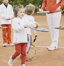 Photo : Trois enfants et un adulte jonglent avec une balle de tennis sur une raquette de tennis.