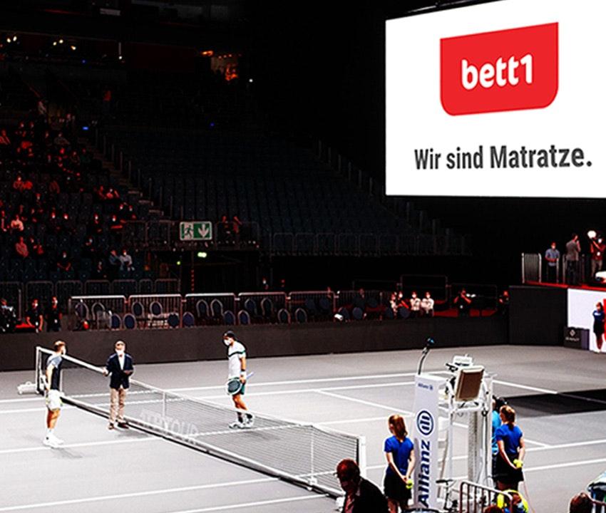 Photo : Dans le bett1HULKS, deux joueurs se font face au filet, le panneau lumineux dans l'arène montre le slogan bett