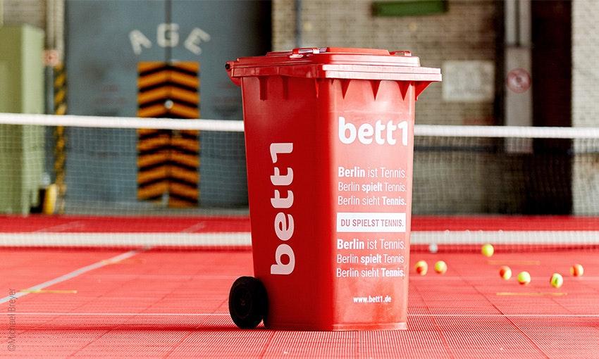 Photo : Un tonneau rouge avec le logo bett1 se trouve sur un court de tennis.