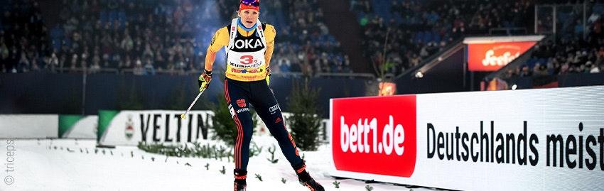 Photo : Une skieuse de fond ; en arrière-plan, une publicité pour le périmètre de bett1.