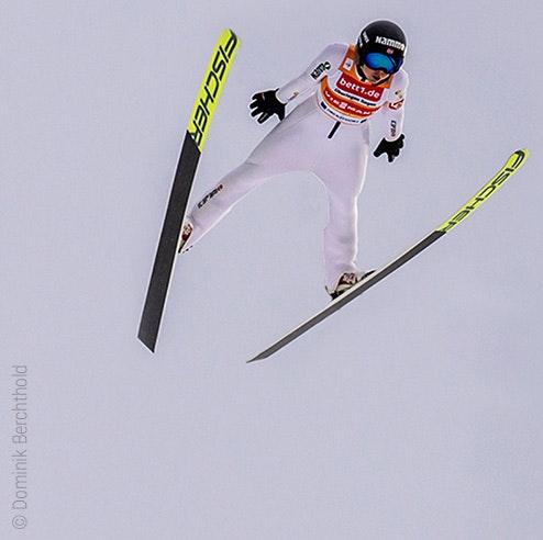 Photo : Un sauteur à ski dans les airs ; publicité pour bett1 sur son maillot.