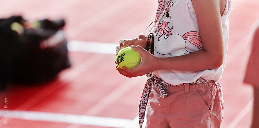 Photo : Un enfant tient une balle de tennis dans sa main.