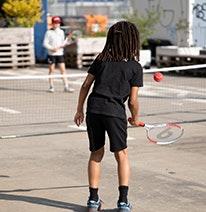 Photo : Un enfant joue une balle de tennis rouge au-dessus du filet à un autre enfant.