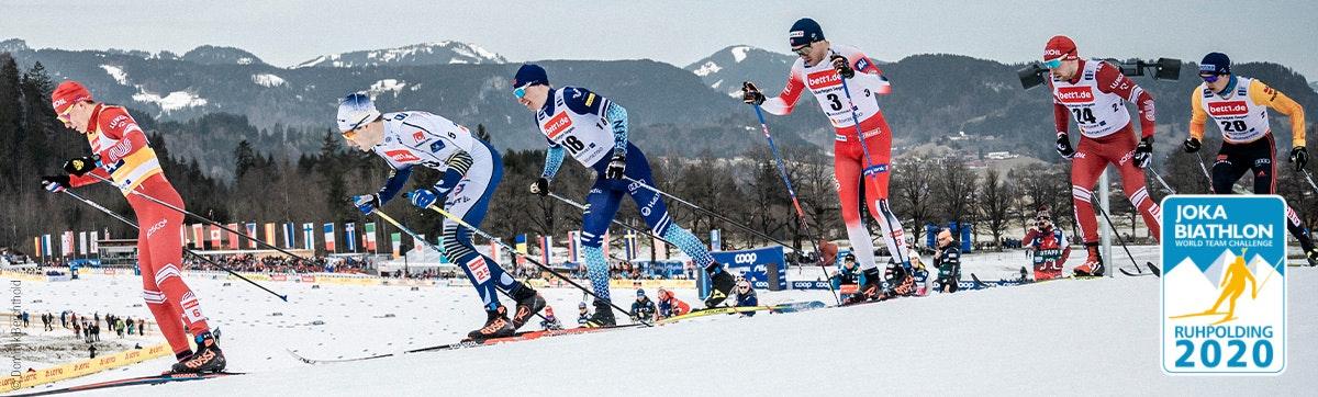Photo : Six skieurs de fond dans la course ; publicité pour bett1 sur leurs maillots.